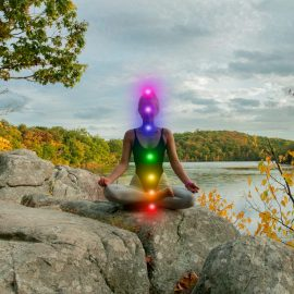 Woman is meditating with glowing seven chakras on stone outdoor. Woman is practicing yoga on the lake. Kundalini meditation.