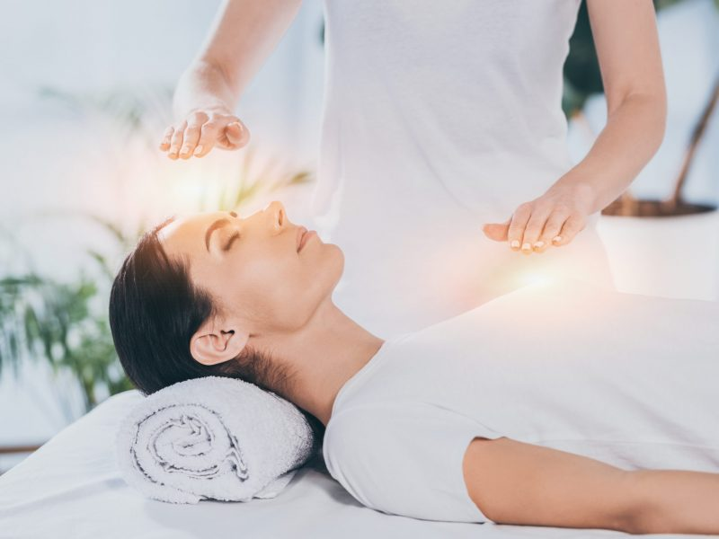 side view of calm young woman receiving reiki healing therapy on head and chest